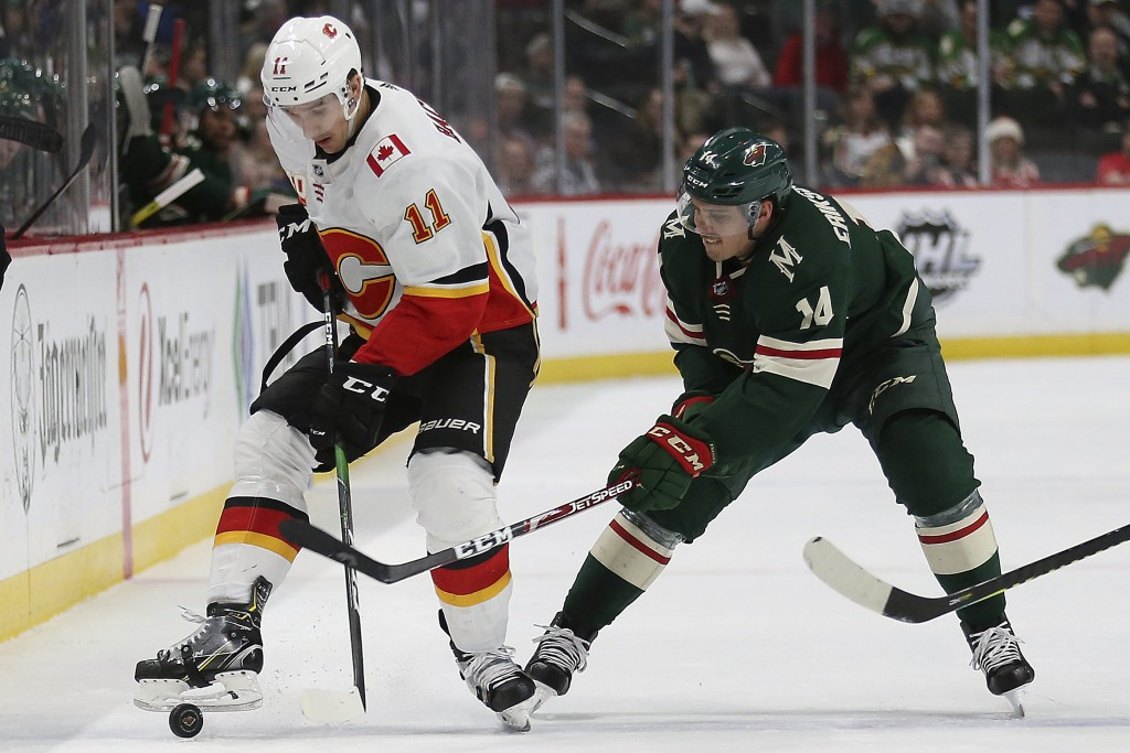 Calgary Flames' Mikael Backlund of Sweden kicks the puck against Minnesota Wild's Joel Eriksson Ek of Sweden in the second period of an NHL hockey gam...