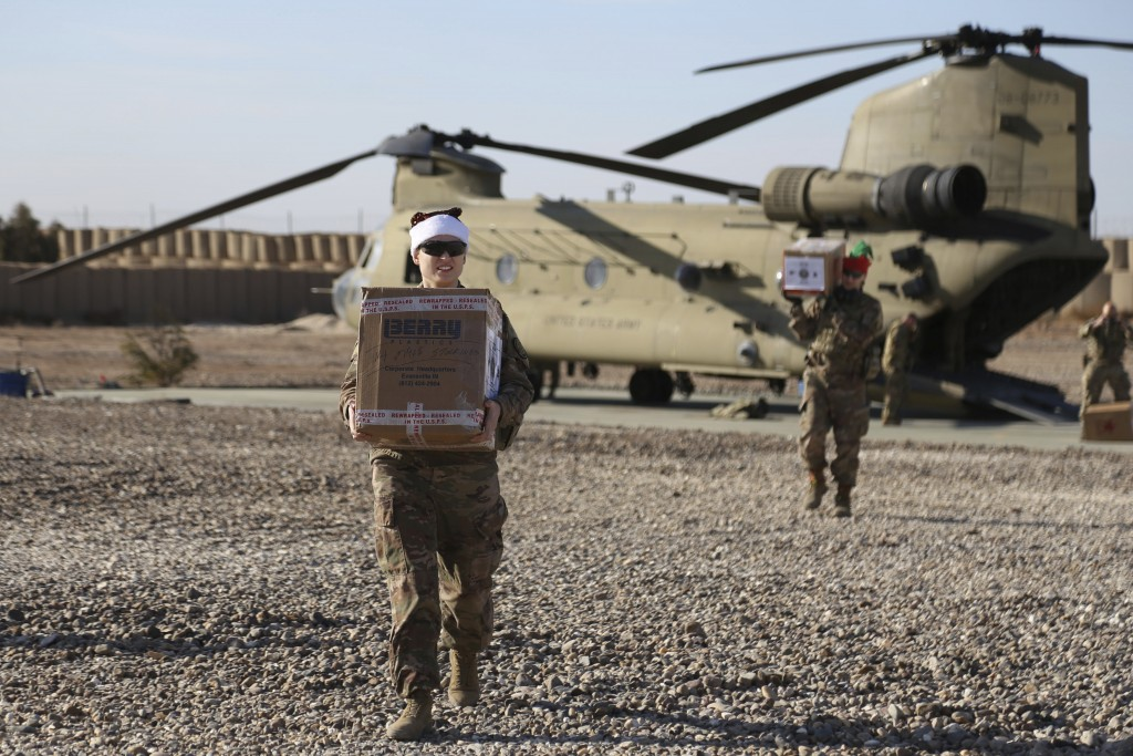 In this Tuesday, Dec. 24, 2019, photo, U.S. service members deliver Christmas gifts to their comrades on a base near the al-Omar oilfield in eastern S...