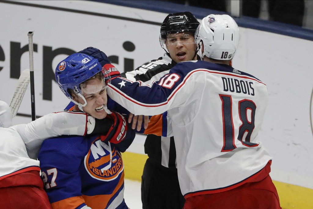 A referee separates New York Islanders' Anders Lee (27) and Columbus Blue Jackets' Pierre-Luc Dubois (18) during the third period of an NHL hockey gam...