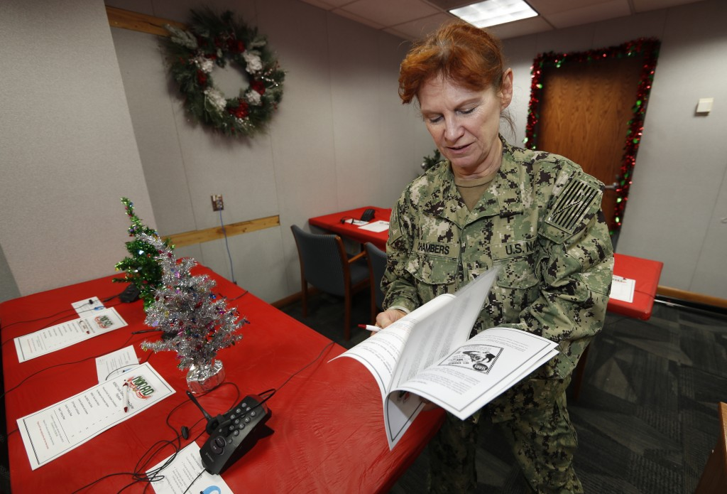 United States Navy Specialist Petty Officer 1st Class Shannon Chambers of Long Beach, Calif., looks over a volunteer playbook in the NORAD Tracks Sant...
