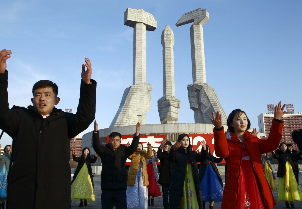 Locals participate in a public dance on the 28th anniversary of the start of Chairman Kim Jong Il's leadership of the Korean People's Army at the Monu...
