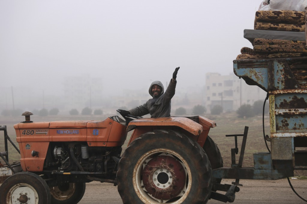A man waves to a photographer as civilians ride in a truck as they flee Maaret al-Numan, Syria, ahead of a government offensive, Monday, Dec. 23, 2019...