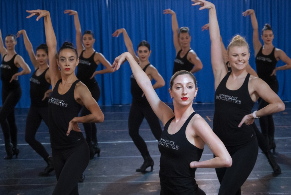 In this Oct. 22, 2019 photo, Rockette Sydney Mesher center right, takes part in a rehearsal at the Rockette's rehearsal space in New York. Mesher, who...