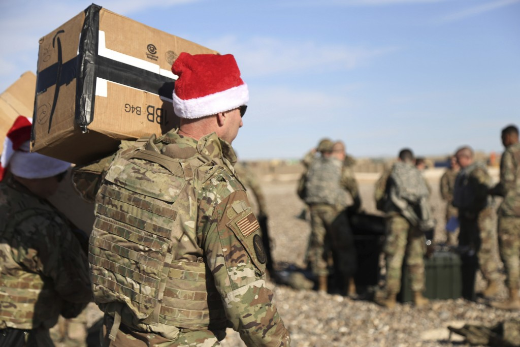 In this Monday, Dec. 23, 2019, photo, a U.S. soldier carries Christmas gifts from a helicopter to deliver to his comrades on a base near the al-Omar o...