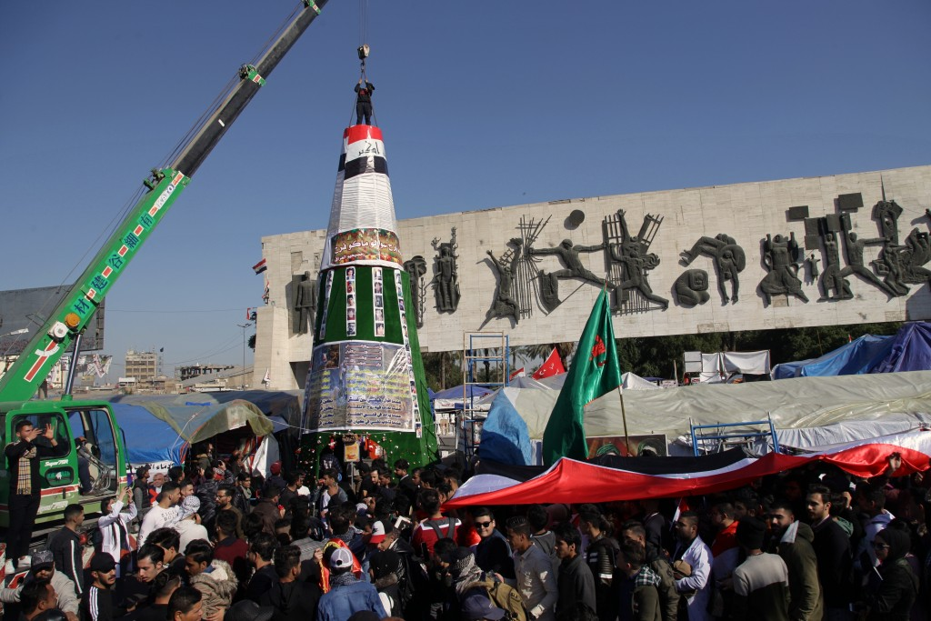 Demonstrators work to install a Christmas tree, with posters of protesters who have been killed in demonstrations and their belongings, while anti-gov...