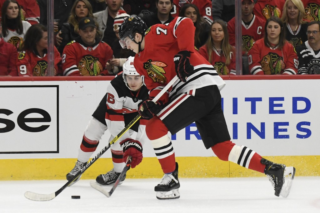 New Jersey Devils center Jack Hughes (86) and Chicago Blackhawks center Kirby Dach (77) go for the puck during the first period of an NHL hockey game ...