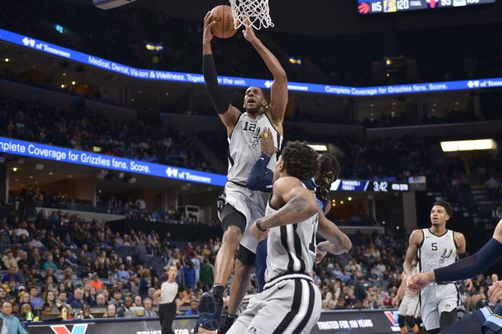 San Antonio Spurs center LaMarcus Aldridge (12) shoots next to Memphis Grizzlies forward Jae Crowder during the second half of an NBA basketball game ...