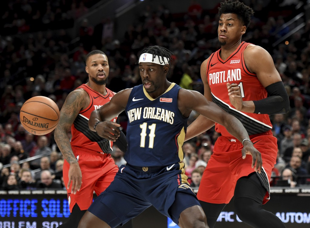 New Orleans Pelicans guard Jrue Holiday, center, loses control of the ball as Portland Trail Blazers guard Damian Lillard, left and center Hassan Whit...