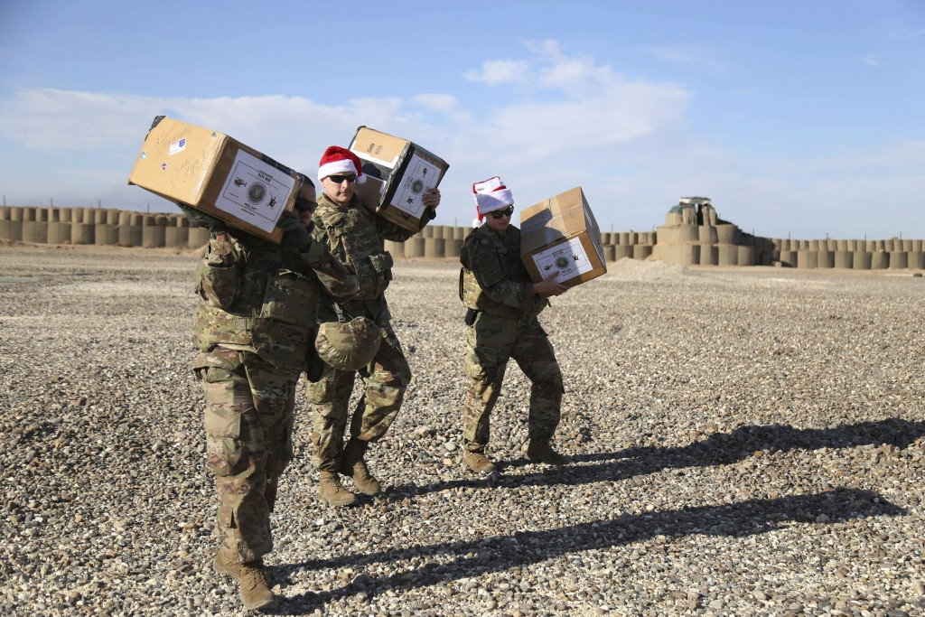 In this Monday, Dec. 23, 2019, photo, U.S. soldiers deliver Christmas gifts to their comrades on a base near the al-Omar oilfield in eastern Syria. It...