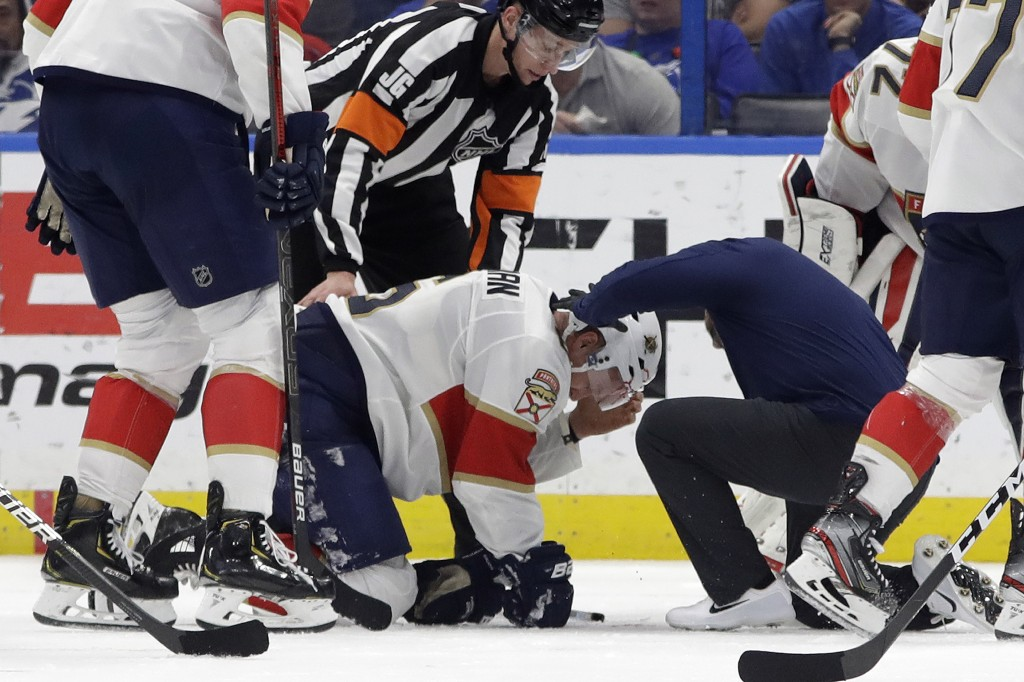 Blood pours out of Florida Panthers defenseman Anton Stralman's helmet after he was hit on the head by a slap shot during the third period of the team...