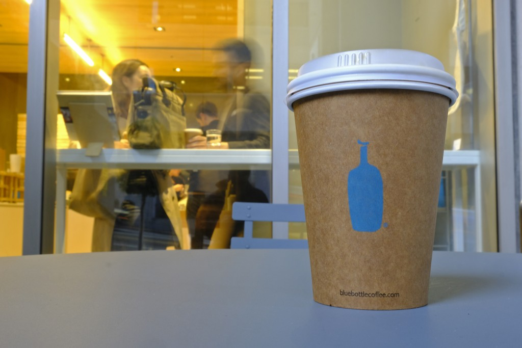 In this Thursday, Dec. 12, 2019 photo, a Blue Bottle Coffee paper to-go cup rests on a table outside one of their cafes in San Francisco. The Oakland-...