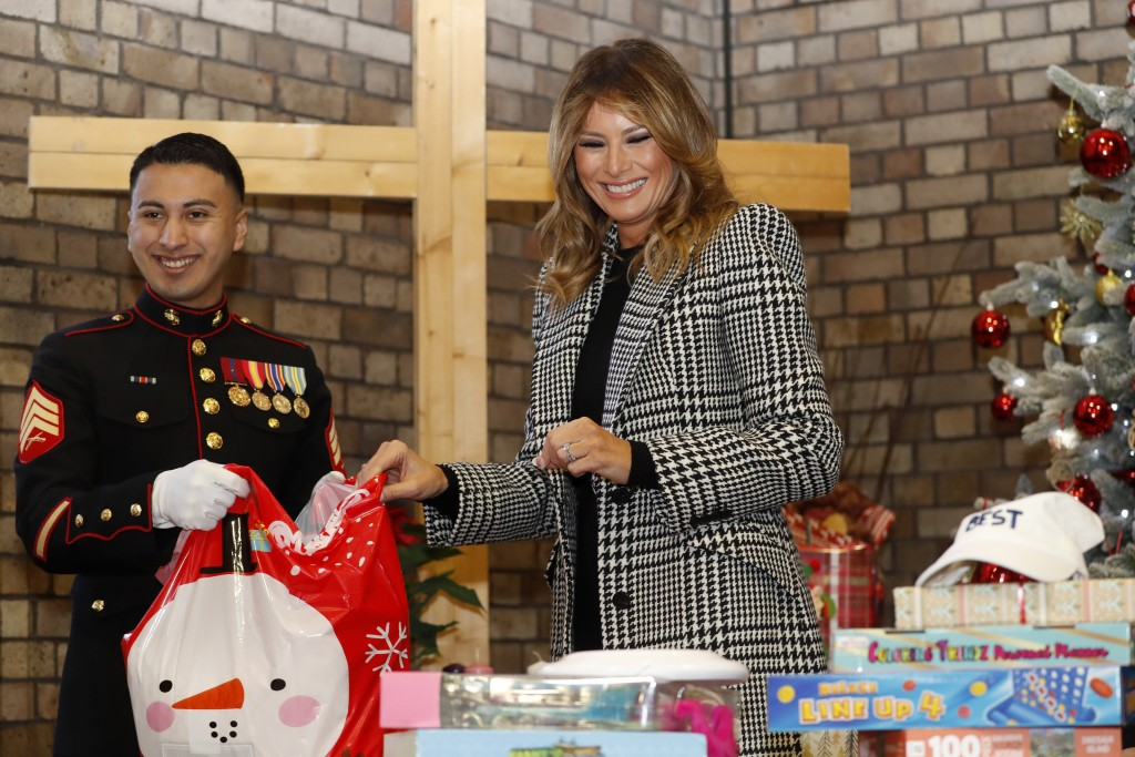 FILE - In this Dec. 4, 2019, file photo first lady Melania Trump joins local students and U.S. Marines stationed at the U.S. Embassy, wrapping holiday...