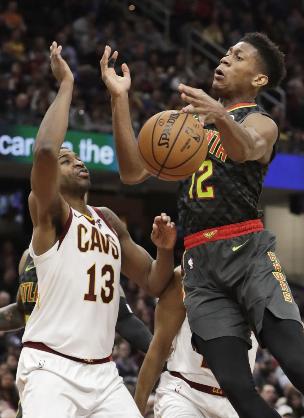 Atlanta Hawks' De'Andre Hunter (12) loses control of the ball as Cleveland Cavaliers' Tristan Thompson (13) defends during the second half of an NBA b...