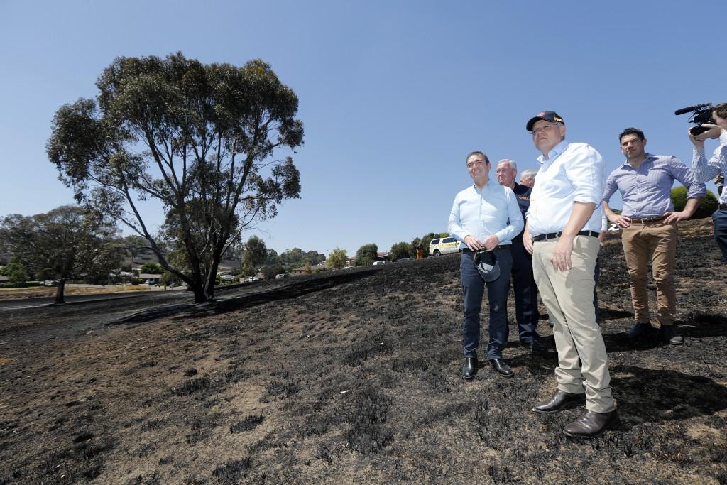 Australian Prime Minister Scott Morrison, front, and SA Premier Steven Marshall, left,  stand on burnt ground of Jacaranda Drive in Woodside, Tuesday,...