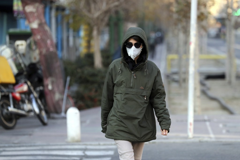 An Iranian woman wears a mask to help guard against dangerous levels of air pollution in Tehran, Iran, Monday, Dec. 23, 2019. Poor air quality forced ...