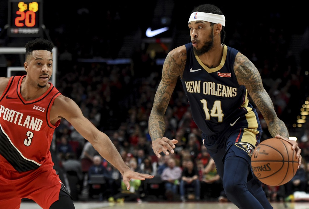New Orleans Pelicans forward Brandon Ingram, right, drives to the basket on Portland Trail Blazers guard CJ McCollum, left, during the first half of a...