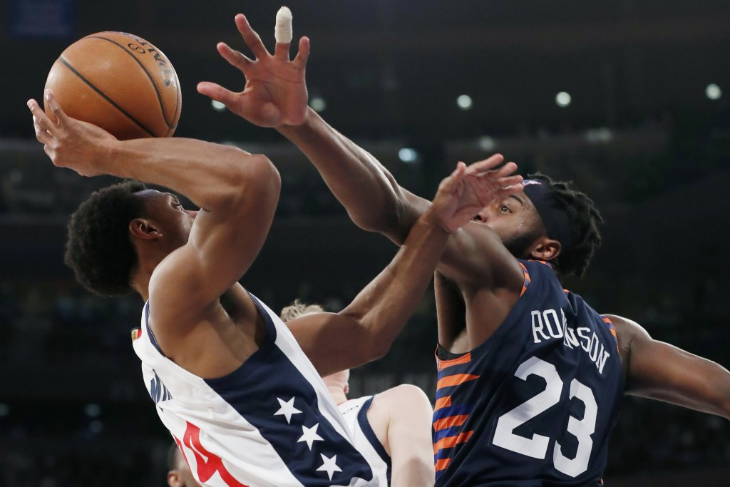 New York Knicks center Mitchell Robinson (23) defends against Washington Wizards guard Ish Smith (14) during the first half of an NBA basketball game ...