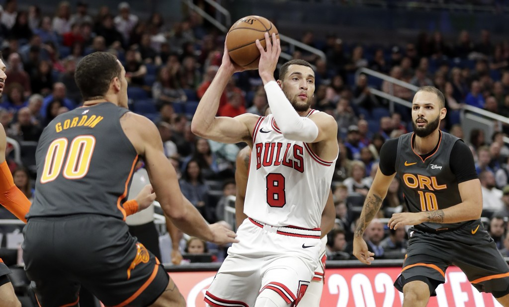 Chicago Bulls guard Zach LaVine (8) passes the ball as he gets between Orlando Magic forward Aaron Gordon (00) and guard Evan Fournier, right, during ...