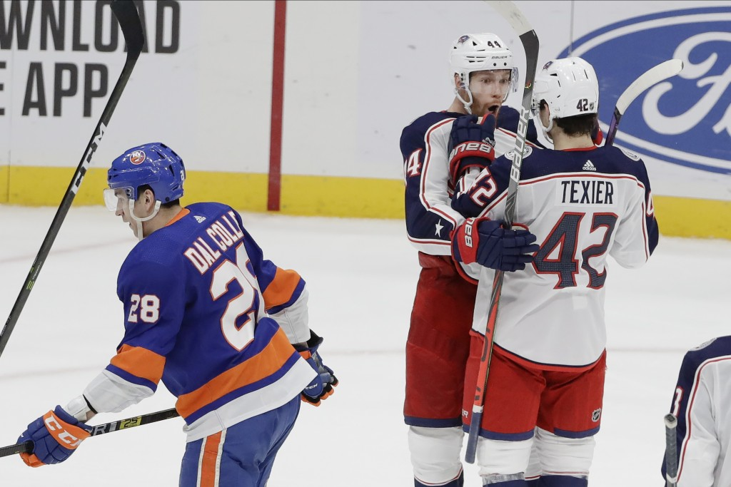 Columbus Blue Jackets' Vladislav Gavrikov (44) celebrates with teammate Alexandre Texier (42) as New York Islanders' Michael Dal Colle (28) skates awa...