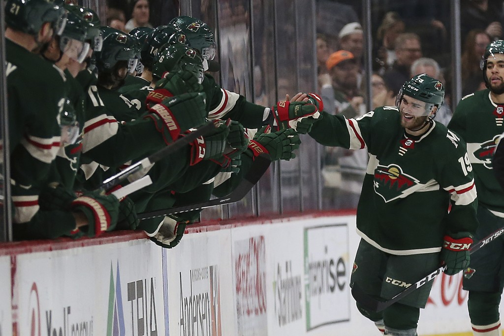 Minnesota Wild's Luke Kunin high fives teammates on the bench after he scored a goal against the Calgary Flames in the second period of an NHL hockey ...