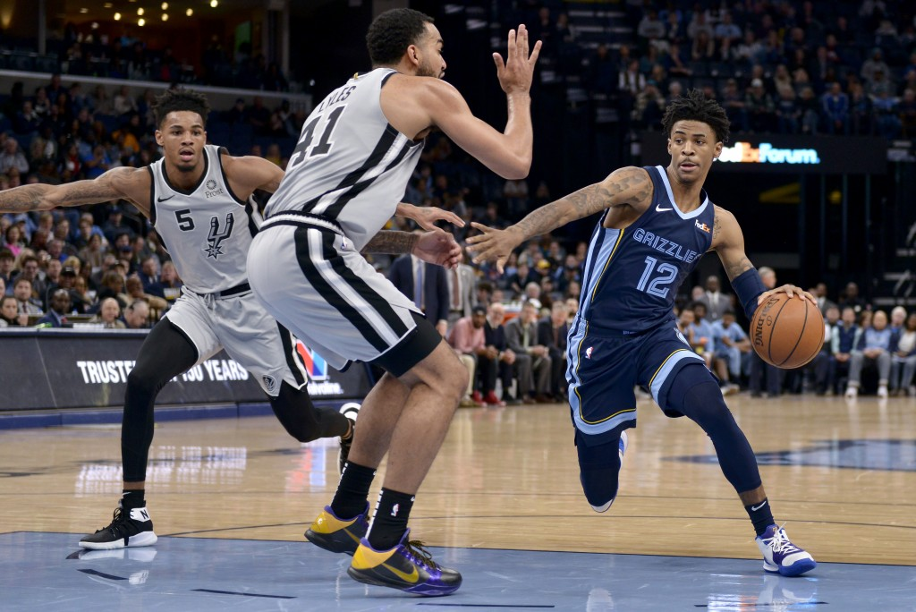 Memphis Grizzlies guard Ja Morant (12) drives around San Antonio Spurs forward Trey Lyles (41) and guard Dejounte Murray (5) during the first half of ...