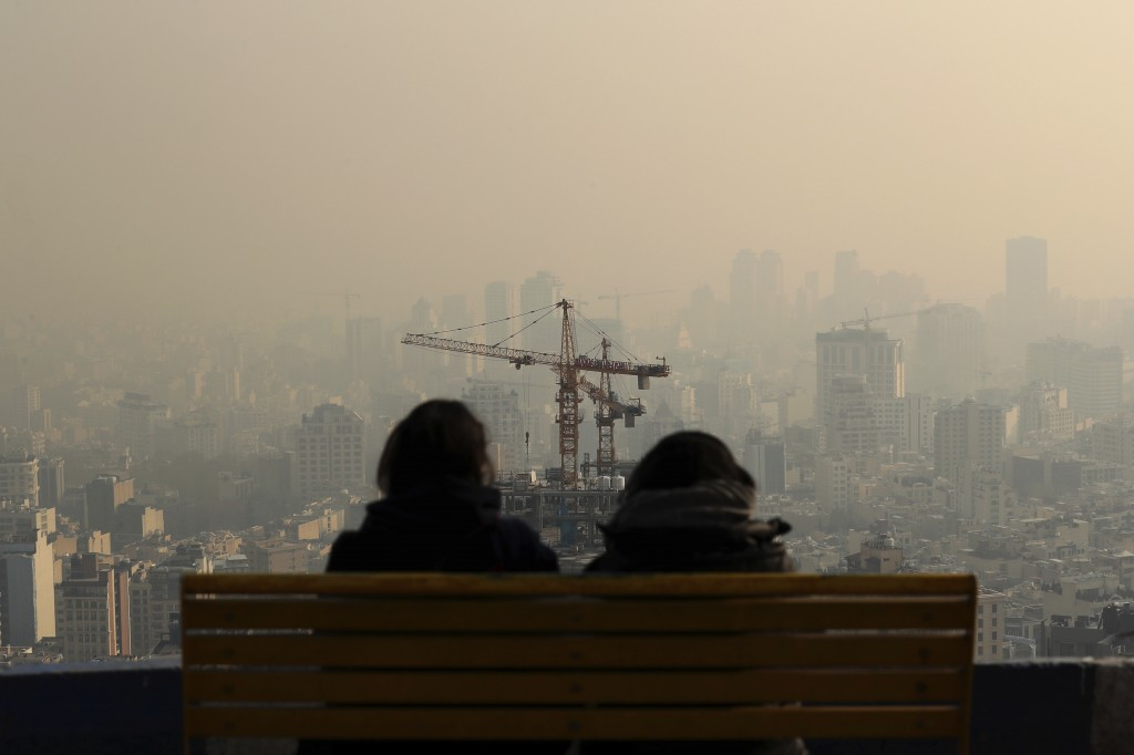 People look at the skyline through polluted air, in the Velenjak mountainous area of Tehran, Iran Monday, Dec. 23, 2019. Dangerously poor air quality ...