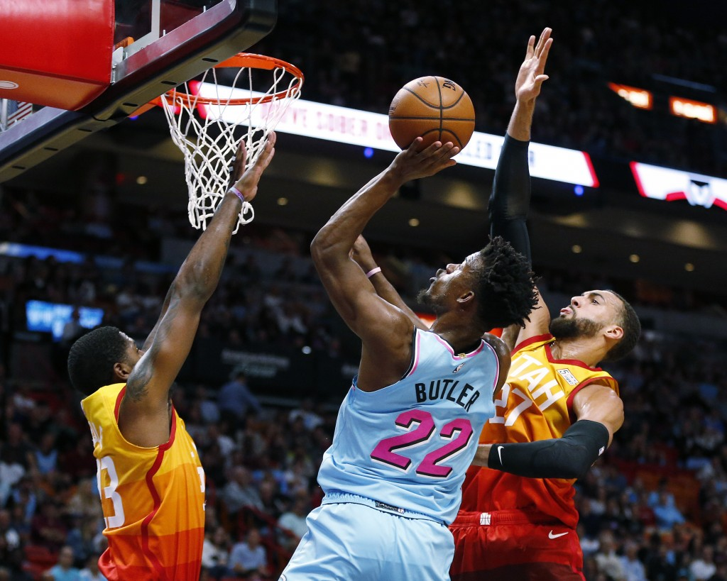 Miami Heat forward Jimmy Butler (22) goes to the basket between Utah Jazz forward Royce O'Neale (23) and center Rudy Gobert (27) during the first half...