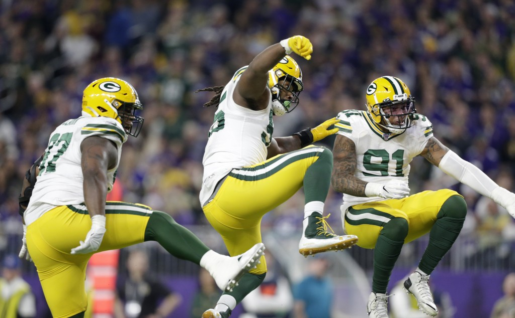 Green Bay Packers' Kenny Clark, left, Za'Darius Smith and Preston Smith, right, celebrate after a sack during the first half of the team's NFL footbal...