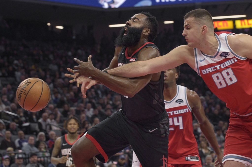 Houston Rockets guard James Harden (13) is fouled by Sacramento Kings forward Nemanja Bjelica (88) during the first half of an NBA basketball game in ...