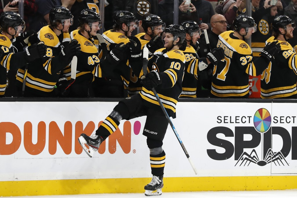 Boston Bruins' Anders Bjork is congratulated at the bench after scoring against the Washington Capitals during the first period of an NHL hockey game ...