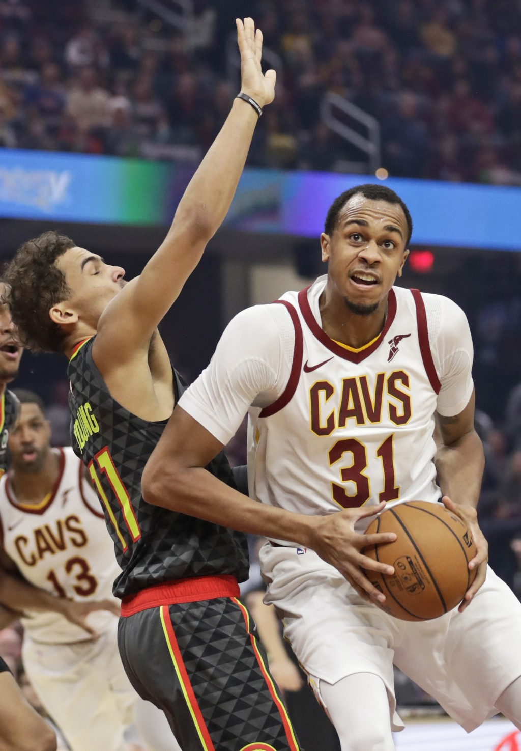 Cleveland Cavaliers' John Henson, right, drives past Atlanta Hawks' Trae Young during the first half of an NBA basketball game Monday, Dec. 23, 2019, ...