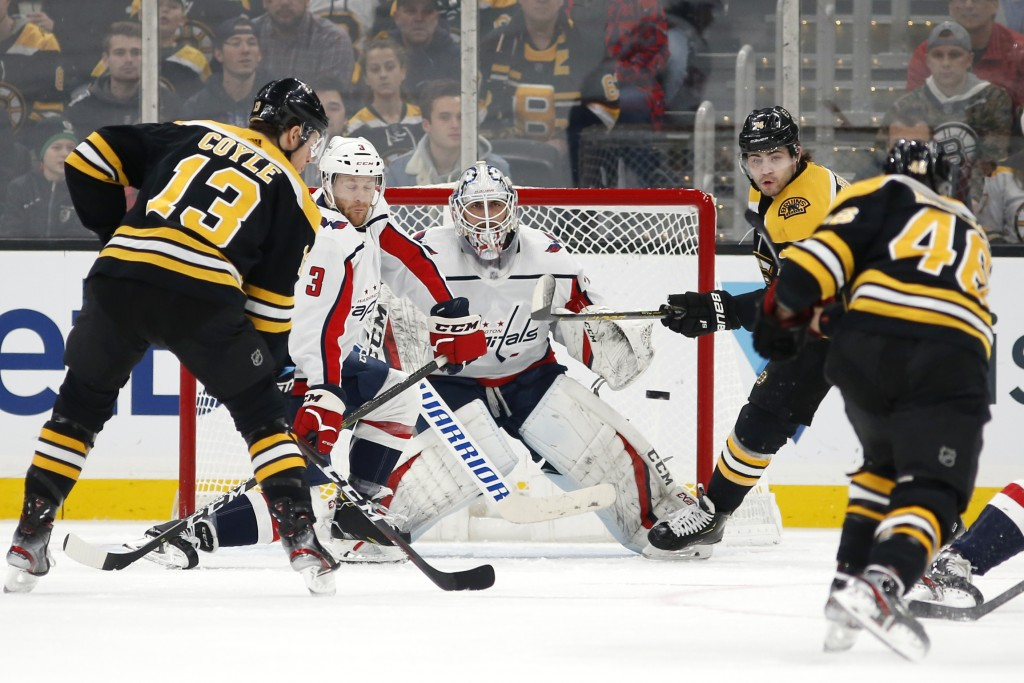 Washington Capitals goaltender Braden Holtby eyes a shot by Boston Bruins' David Krejci (46) as Jake DeBrusk and Charlie Coyle (13) wait in front of t...