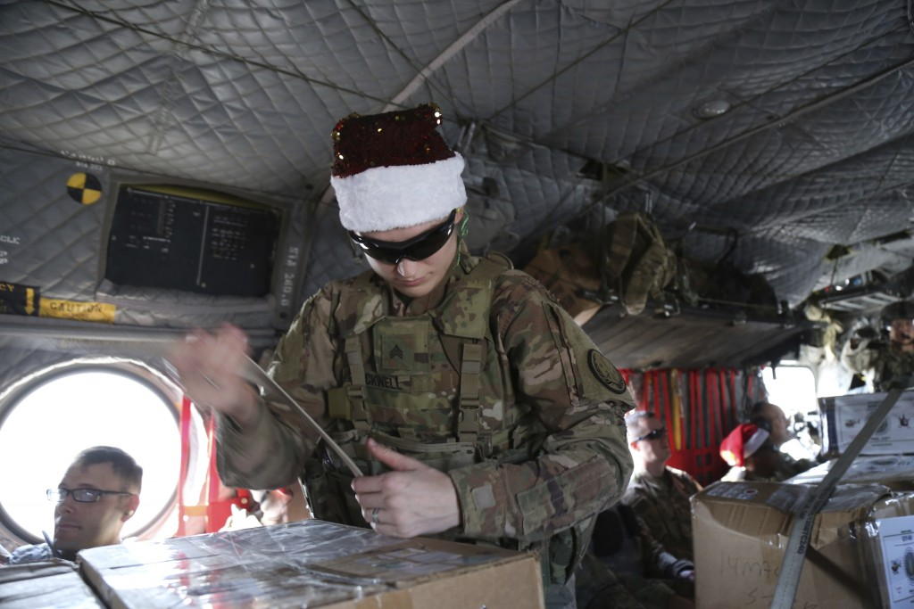 In this Monday, Dec. 23, 2019, photo, a U.S. soldier secures Christmas gifts on a helicopter in Irbil, Iraq bound for American bases in eastern Syria....