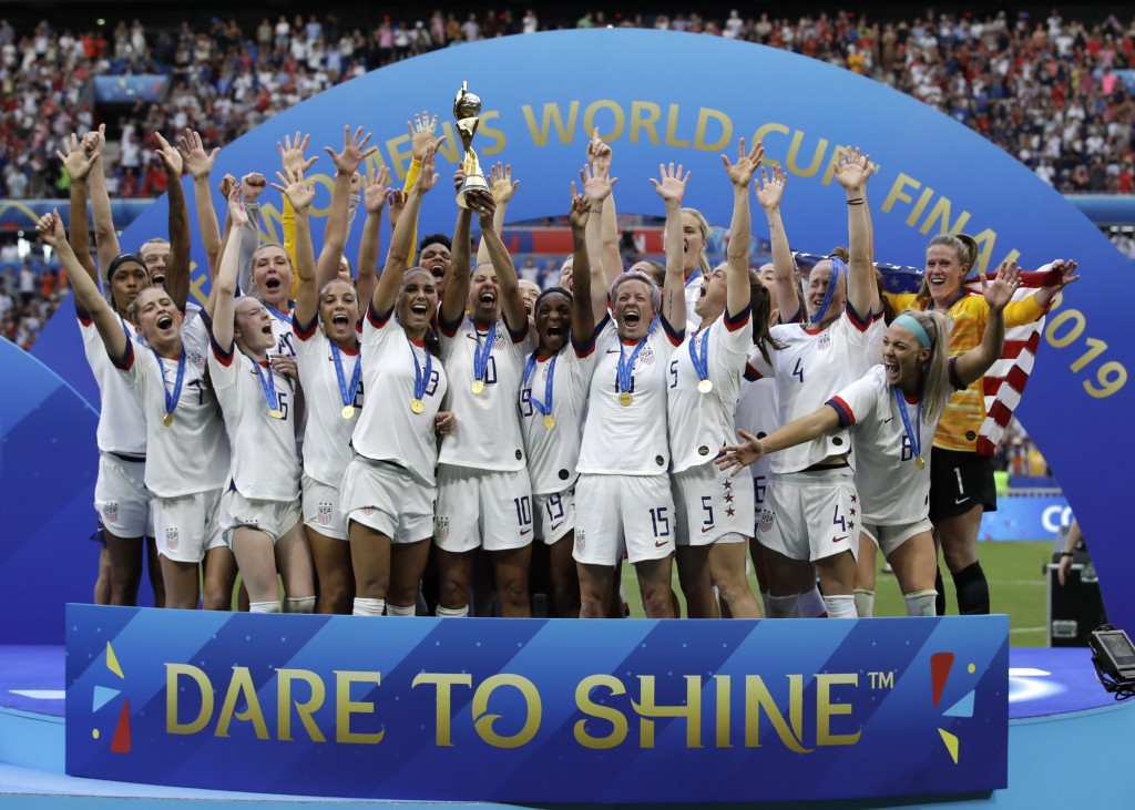 File-This July 7, 2019, file photo shows the United States' team celebrating with the trophy after winning the Women's World Cup final soccer match be...