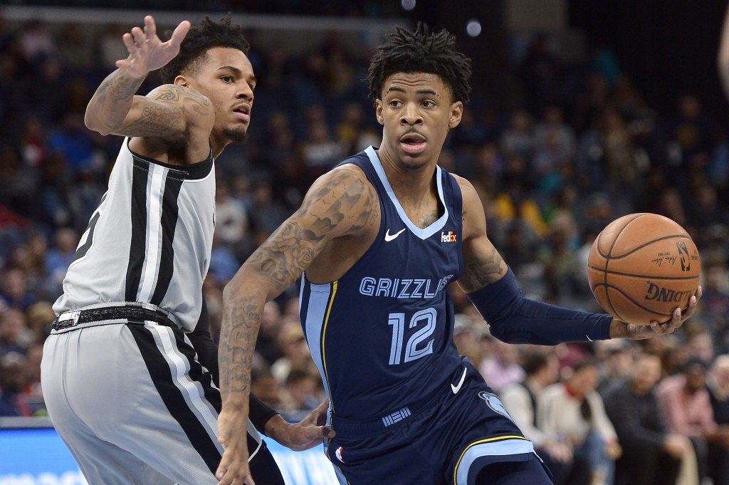 Memphis Grizzlies guard Ja Morant (12) handles the ball as San Antonio Spurs guard Dejounte Murray defends during the first half of an NBA basketball ...
