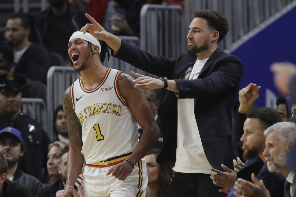 Injured Golden State Warriors guard Klay Thompson, right, and guard Damion Lee (1) react after Alec Burks scored during the first half of the team's N...