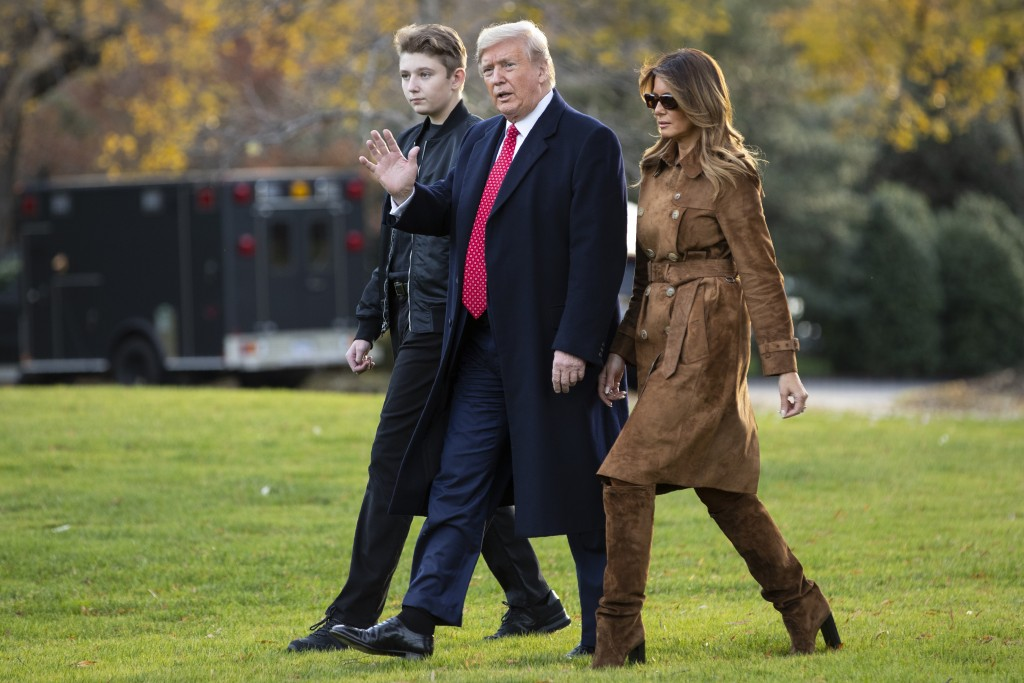 FILE- In this Nov. 26, 2019, file photo, President Donald, first lady Melania Trump, and Barron Trump, walk to board Marine One on the South Lawn of t...
