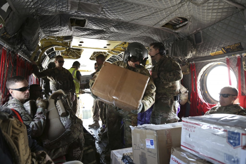 In this Monday, Dec. 23, 2019, photo, U.S. soldiers load Christmas gifts onto a helicopter in Irbil, Iraq bound for American bases in eastern Syria. I...