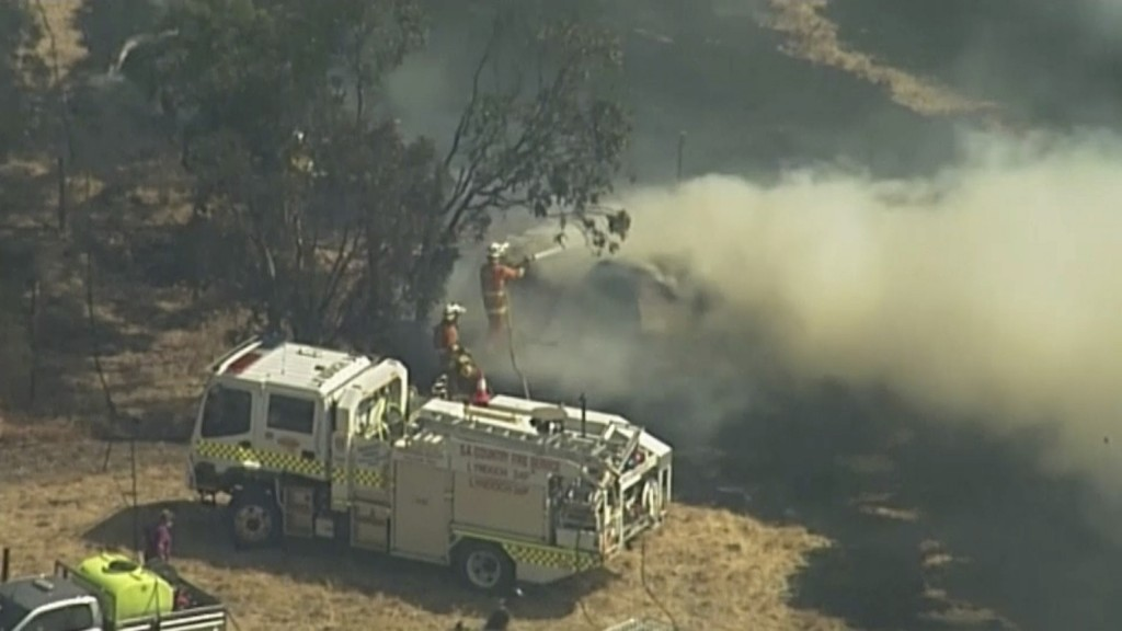 In this image made from video, an aerial scene shows firefighters spray water on rising smoke  in Birdwood, South Australia, Wednesday, Dec. 25, 2019....