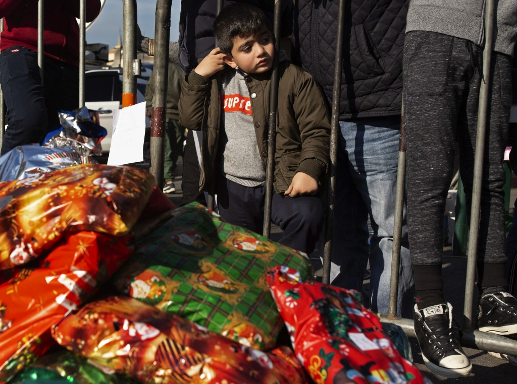 In this Sunday, Dec. 22, 2019 photo, a little boy waits for a Christmas present as anti-government protesters distribute gifts to the needy, at Martyr...