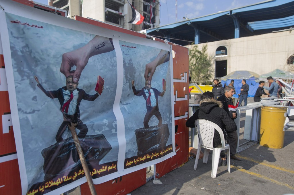 Protesters go through security inspection next to posters that depicts Qusay al-Suhail, a candidate for the prime minister's post, and Arabic that rea...