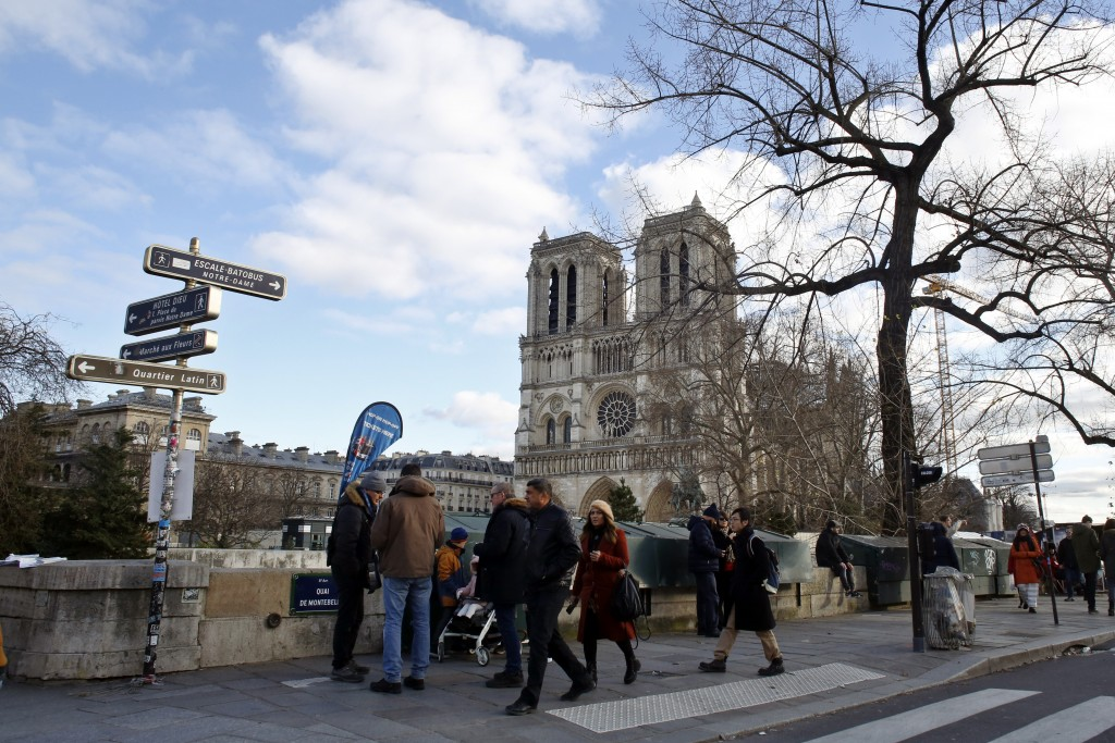 People walk on the Seine river banks, near Notre Dame cathedral, in Paris, Wednesday, Dec. 25, 2019. The rector of Notre Dame Cathedral says the Paris...
