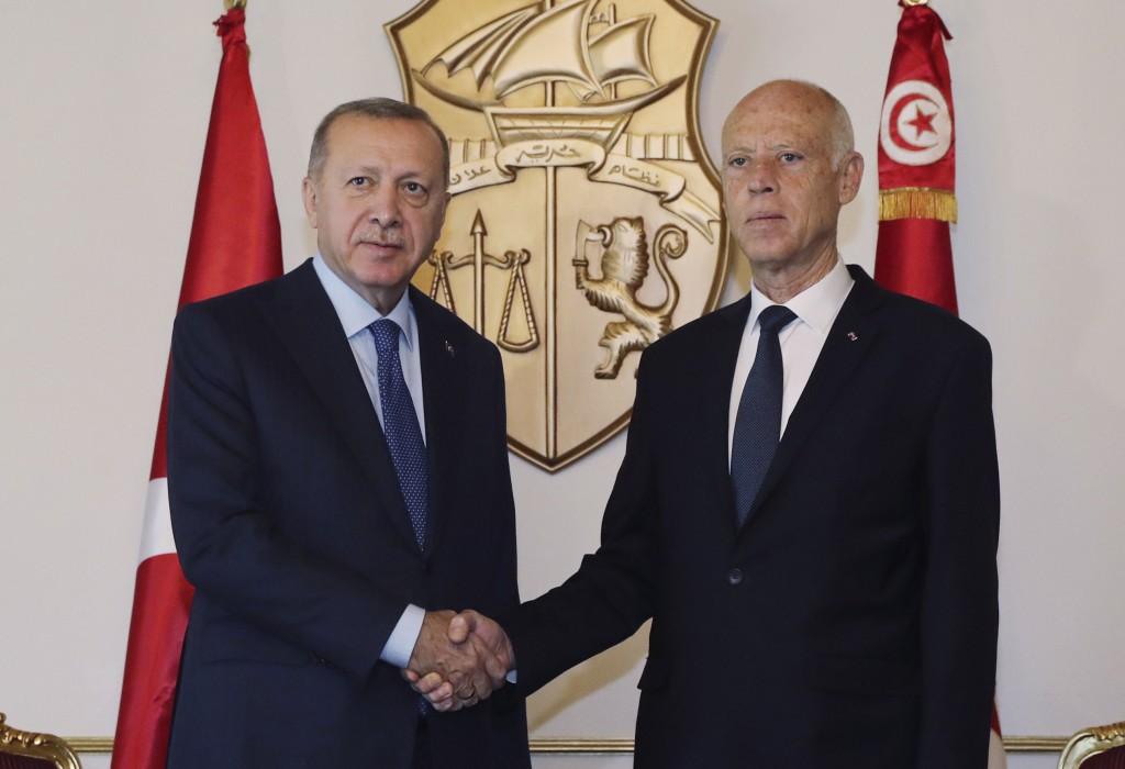 Turkey's President Recep Tayyip Erdogan, left, and Tunisian President Kais Saied shake hands before a meeting, in Tunis, Tunisia, Wednesday, Dec. 25, ...