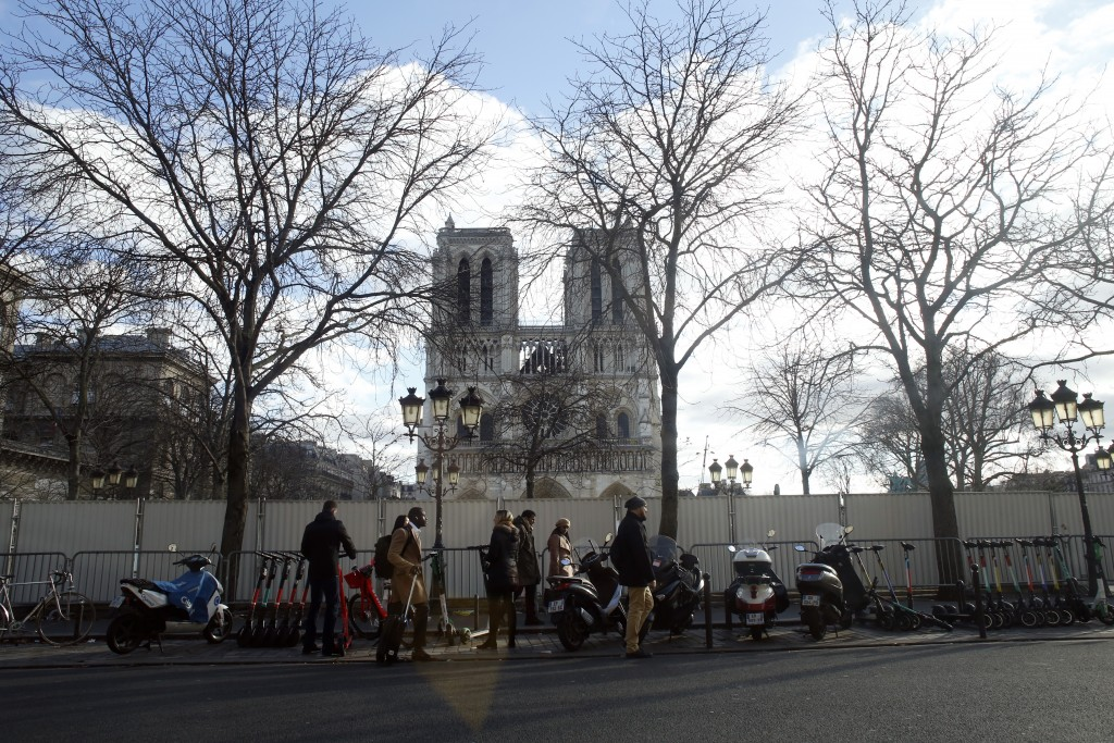 People walk in front of Notre Dame cathedral, in Paris, Wednesday, Dec. 25, 2019. The rector of Notre Dame Cathedral says the Paris landmark is still ...