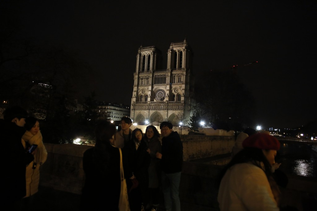 Tourists take selfies in front of Notre Dame cathedral in Paris, Tuesday, Dec. 24, 2019. Notre Dame Cathedral is unable to host Christmas services for...
