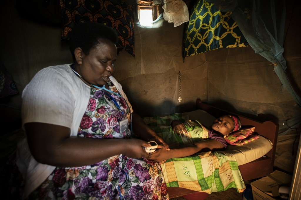 In this photo taken Tuesday, Nov. 5, 2019, palliative care nurse Madeleine Mukantagara, 56, left, uses a pulse-oximeter to check on the health of Vest...