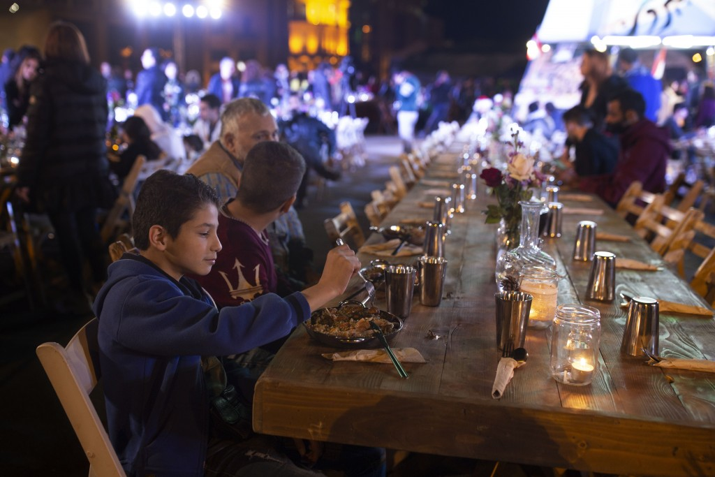 In this Monday, Dec. 23, 2019 photo, a boy eats with his brother and father at a public Christmas dinner in Martyrs Square where anti-government activ...