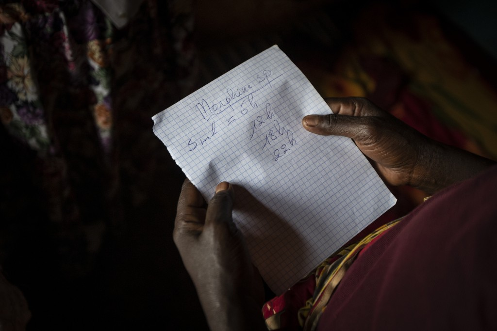 In this photo taken Monday, Nov. 4, 2019, Maria Mukamabano holds a handwritten note advising the schedule that her mother-in-law and cancer patient At...