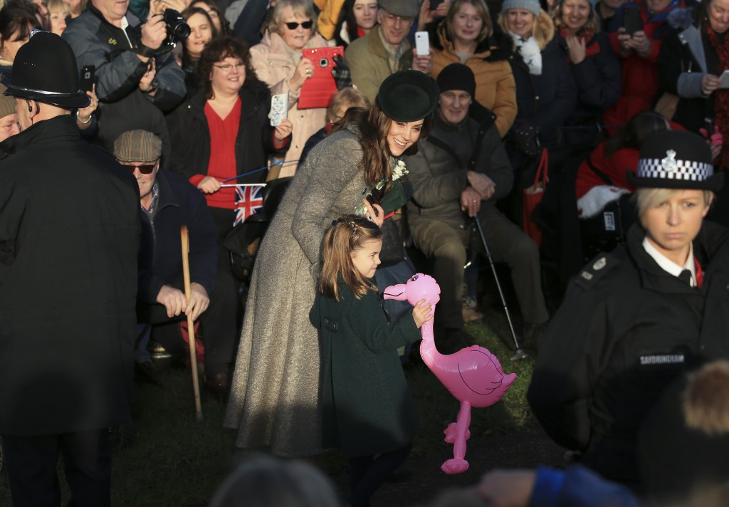 Britain's Catherine, Duchess of Cambridge, center left, speaks with her daughter Princess Charlotte as she holds a pink flamingo while greeting the pu...