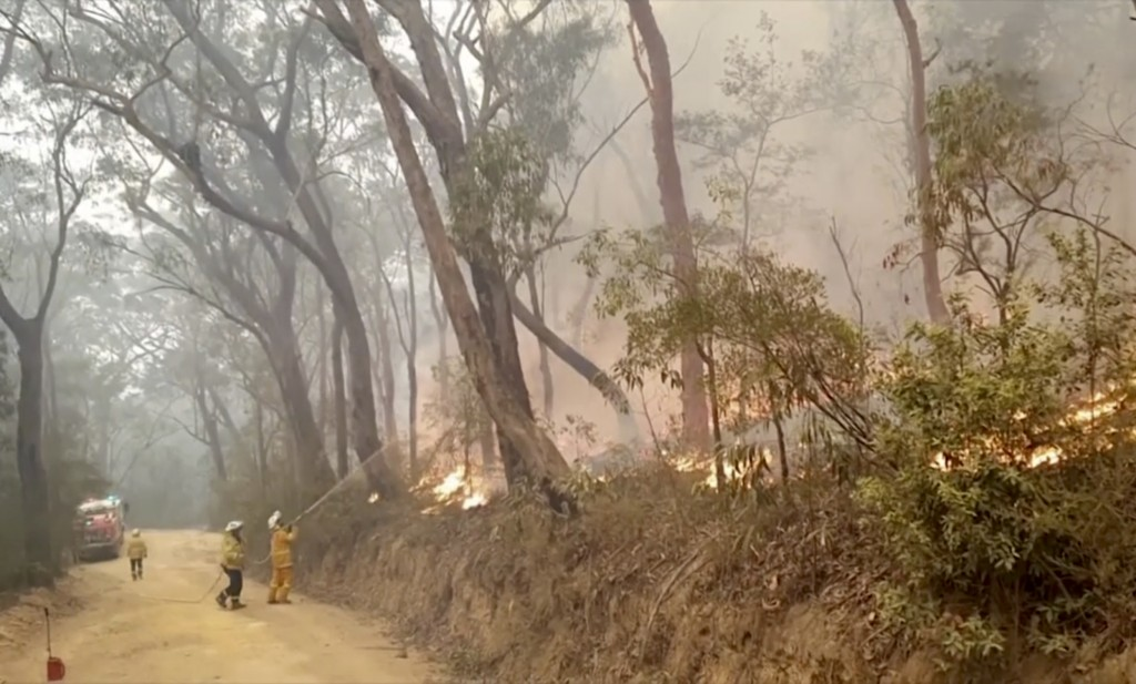 In this image made from video taken on Dec. 23, 2019, and provided Dec. 25, 2019, by Ingleside Rural Fire Brigade, fire brigade volunteers trying to t...